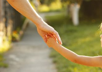 close up of parent holding hands with child and walking outside.