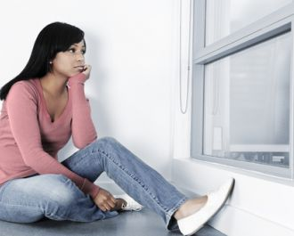 woman in delayed divorce sitting by the window looking unhappy .