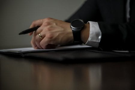 divorce lawyer sat at wooden table with pen and paperwork